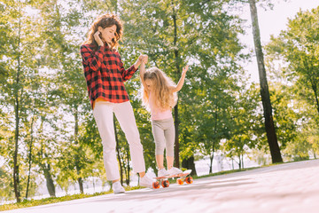 woman holding girls hands while she riding skateboard in the park