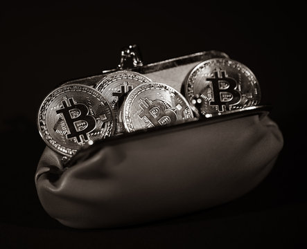 Metal Bitcoins in leather wallet on black background