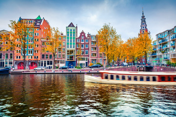 Photo sur Aluminium Amsterdam Stunning autumn cityscape of Amsterdam. Famous Dutch channels and excursion boat. Colorful morning landscape in Netherlands, Europe. Traveling concept background..