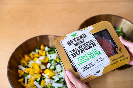 Aspen, USA - June 29, 2019: Beyond meat plant-based protein package with woman holding brand by salad bowls