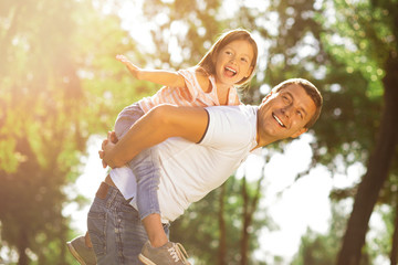 happy daughter piggyback riding her daddy in the park on sunny day