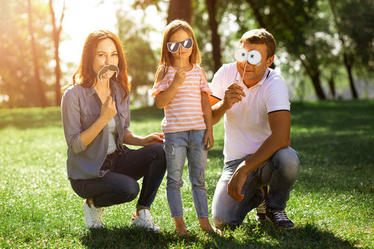 family of three using funny paper masks on the sticks outdoors and looking at the camera