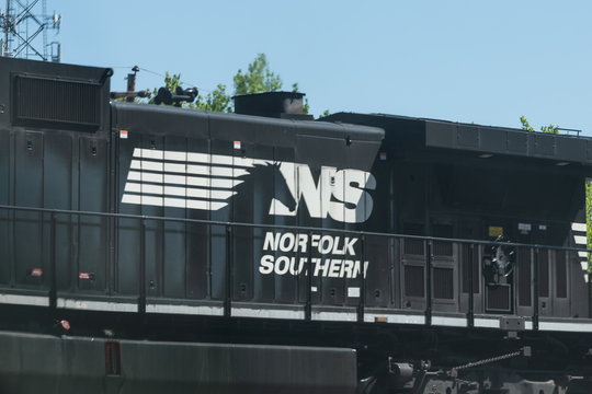 Atlanta, USA - April 20, 2018: Norfolk Southern locomotive cargo freight train with cars passing on railroad tracks in Georgia downtown midtown city in summer