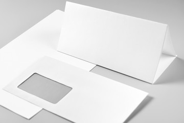 Blank Folded Sheet of Paper, Letterhead, or Flyer and Envelope over Stack of Paper