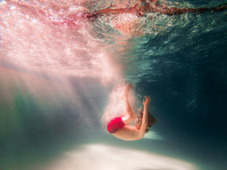Underwater view of a boy jumping into a swimming pool