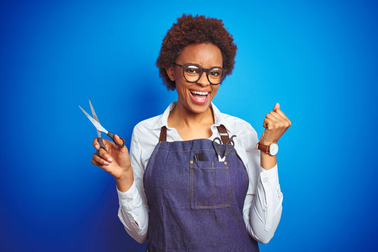 African american hairdresser woman holding scissors over blue isolated background screaming proud and celebrating victory and success very excited, cheering emotion