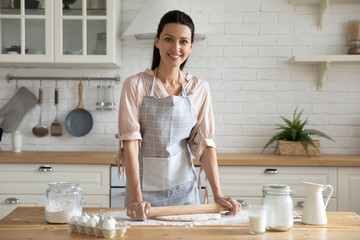 Portrait of happy brunette woman in apron, rolling out dough.