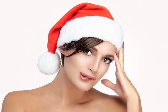 Cute young woman in a red Christmas Santa hat biting her lip