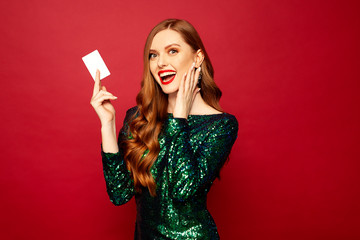 beautiful red-haired model stands on a red background and smiles a beautiful smile in brilliant...