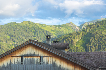A small town at the foot of the mountains. Austrian village in a valley between the mountains. Rural landscape. Wooden roofs of houses. View of the Alps from the village. House in the mountains.
