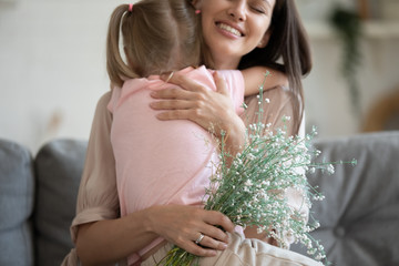 Cropped image focus on flowers, excited young mother cuddling daughter.