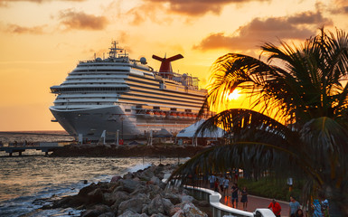 WILLEMSTAD, CURACAO - APRIL 04, 2018:  Cruise ship Carnival Conquest docked at port Willemstad on sunset.