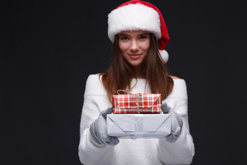 Young beautiful smiling girl in red Santa hat holding gift boxes on a dark background. Xmas fashion model with long straight hair. Winter holidays, Christmas, New Year concept.