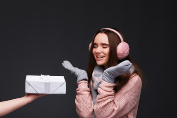 Happy excited young beautiful smiling girl in knitting pullover and pink fluffy earmuffs with gift boxes. Xmas model with long straight hair. Winter holidays, Christmas, New Year concept.