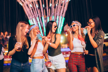 Foto op Aluminium Amusementspark Female friends eating cotton candy and drinking beer in amusement park