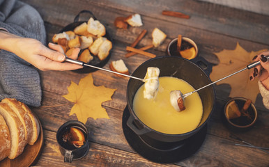 Top view friends cooking Swiss fondue assorted cheeses dinner on fire, hands holding mulled wine background wood board