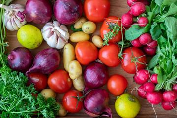 vegetables overhead close up image, radish onions garlic parsley tomatoes lemon patatoes