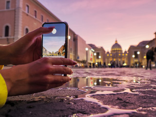 Young woman traveler tourist taking beautiful landscape photo of european sunset during holiday vacation