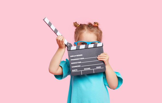 Funny smiling child girl in cinema glasses hold film making clapperboard isolated on pink background. Studio portrait. Childhood lifestyle concept. Copy space for text.