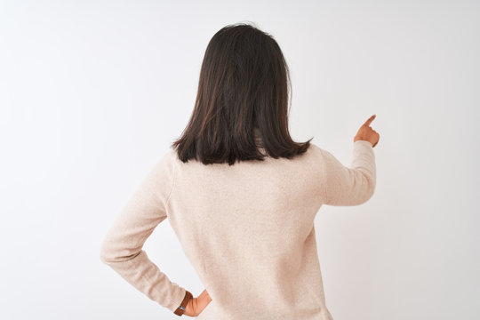Beautiful chinese woman wearing turtleneck sweater standing over isolated white background Posing backwards pointing ahead with finger hand
