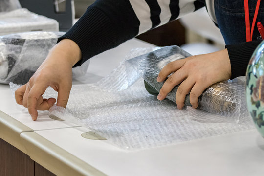 Female vendor hands wrapping a product with bubble film protective at a store's counter, indoors.