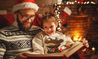 Christmas Eve. family father and child reading magic book at home .