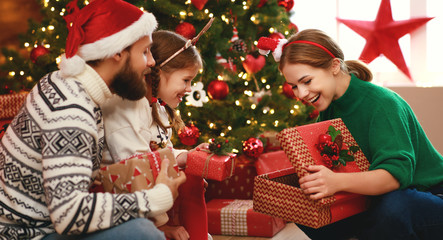 happy family mother, father and child  with gifts near   Christmas tree at home
