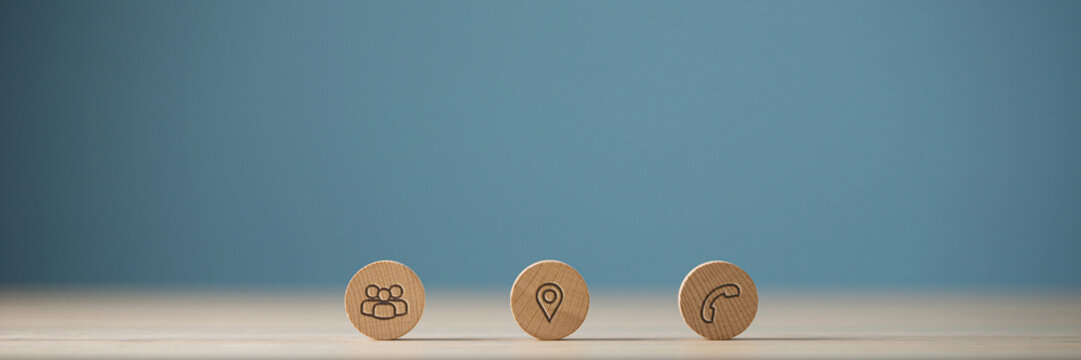 Wide view image of three wooden cut circles with contact and information icons on them