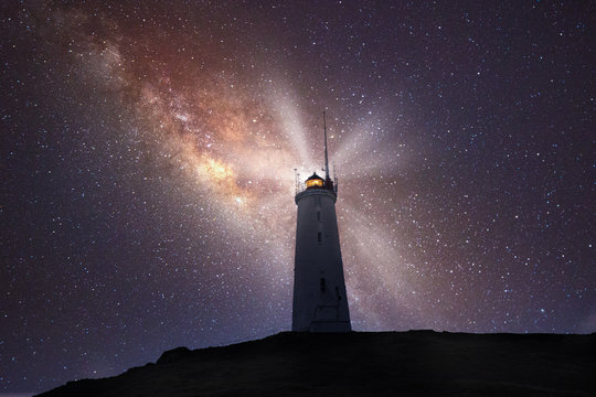 lighthouse shines bright in a night sky of stars