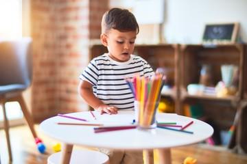 Beautiful toddler boy drawing cute draw using colored pencils at kindergarten