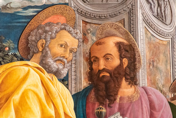 Detail of colorful medieval religious painting showing two holy men talking