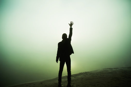 Business success concept. Silhouette of businessman on fog background. Man raise hand against dawn. Man silhouette in costume. Freedom concept with copyspace. Life success. Win contest. Lonely figure