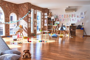 Picture of preschool playroom with colorful furniture and toys around empty kindergarten