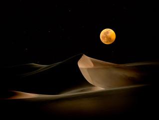 Moon over desert sand dunes, California, USA