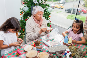 Grandmother teaching her granddaughters how to make christmas Nativity crafts - Real family