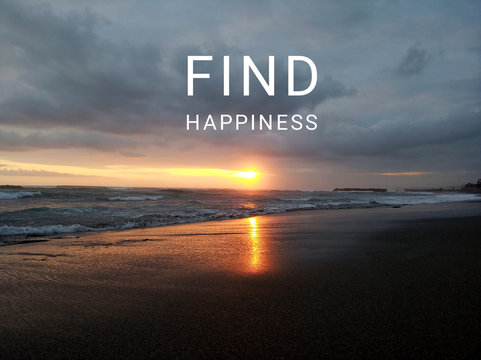 Inspirational motivational quote - Find Happiness. With blurry image of beach landscape, sunset light over horizon, and gloomy dramatic sky over the sea background.