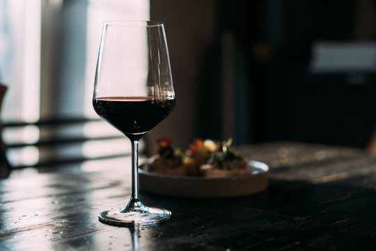 Glass with red wine on the wooden table in the bar