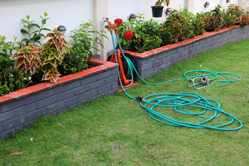 watering hose equipment in green grass of backyard