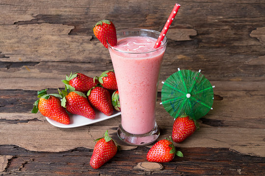 Strawberry and banana smoothie colorful fruit juice milkshake blend beverage healthy high protein the taste yummy In glass drink episode morning on a wooden background.