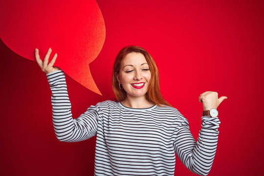 Young beautiful redhead woman holding speech bubble over red isolated background pointing and showing with thumb up to the side with happy face smiling