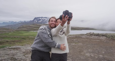 Aufkleber - Iceland couple selfie wearing Icelandic sweaters in beautiful nature landscape on Iceland with camera. Woman and man model in typical Icelandic sweater. Multiracial couple, Asian woman, Caucasian man.