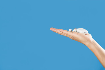 airpods and charging case on a hand isolated on a light blue background
