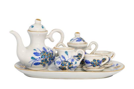 A ceramic tea set with tea pot, sugar jar and cups. The design of porcelain is blue and gold flower hand paint. Isolated on white background with clipping path