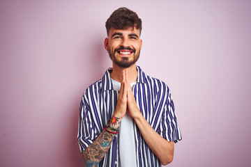 Young man with tattoo wearing striped shirt standing over isolated pink background praying with hands together asking for forgiveness smiling confident.