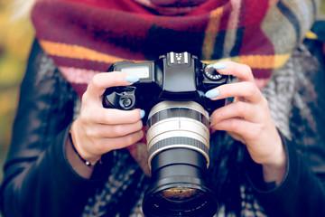 Eine junge Frau hält eine Kamera in den Händen