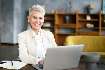 Successful fifty year old businesswoman with short blonde hair and radiant smile communicating online using WiFi on laptop, working at desk, typing commercial offer. Age, technology and lifestyle