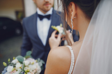 A young and beautiful bride is standing near house with her husband