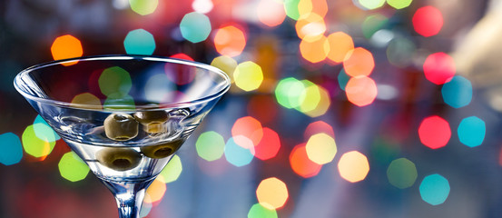 concept of a bachelorette party and birthday celebrations. Dirty martini cocktail on a multicolored bokeh background.