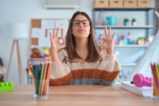 Young beautiful teacher woman wearing sweater and glasses sitting on desk at kindergarten relaxed and smiling with eyes closed doing meditation gesture with fingers. Yoga concept.