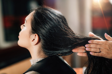 Hairstylist Applying Revitalizing Oil Drops on Woman's Hair